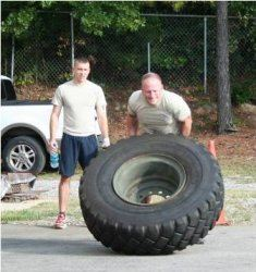 Trainee Lifting a Huge Tire While Being Spotted by Another Member